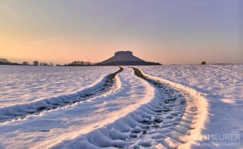 Sonntagsspaziergang durch den Schnee bei Sonnenuntergang mit Blick auf den Lilienstein by Achim Meurer.