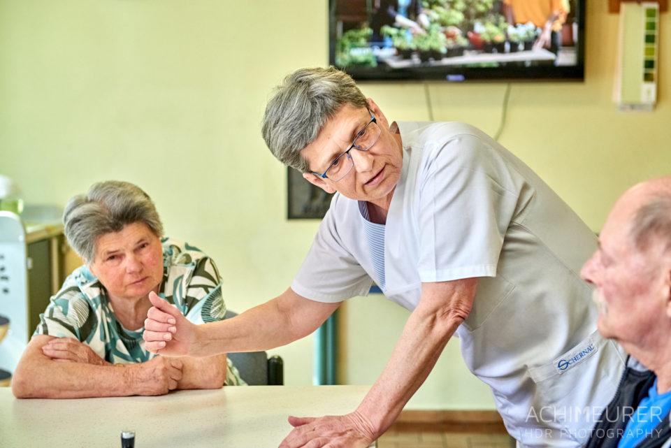 Eine Pflegerin beugt sich zu einem Bewohner und erklärt etwas mit einer Handgeste Schernau-2018_5415 by AchimMeurer.com.