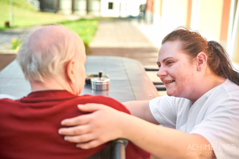 Eine Pflegerin wendet sich einem Bewohner zu und berührt ihn mit der Hand Schernau-2018_5605 by AchimMeurer.com.