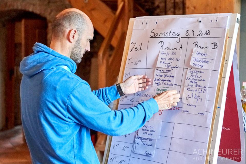 Ein Barcampteilnehmer steht vor dem Sessionplan