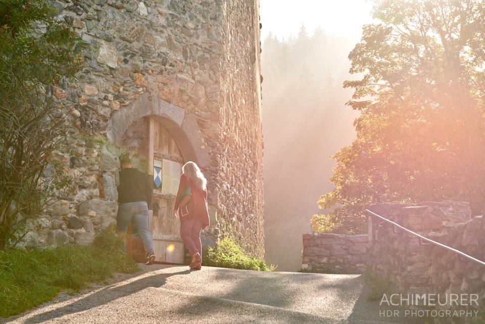 Eine Frau geht auf ein Burgtor zu durch den Nebel