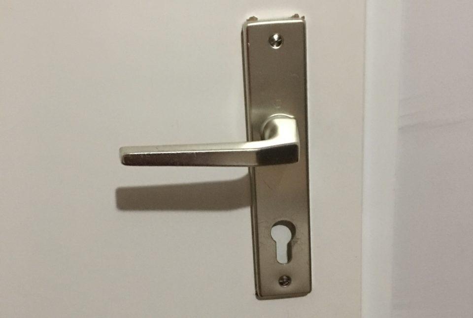Eine Türklinke ist nicht richtig an der Tür angebracht. Es fehlt das Schloss.