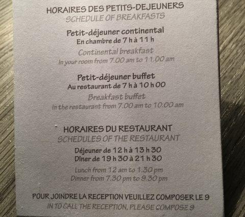 Informationen auf Französisch zu Frühstück- und Restaurantzeiten auf einer kleinen Karte