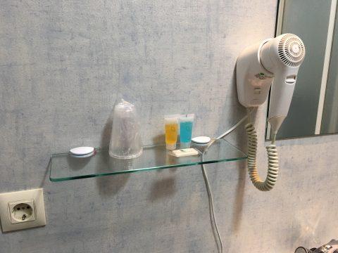 Ablage im Bad mit Zahnputzbechern, Shampoo und Seife. Daneben hängt ein Fön