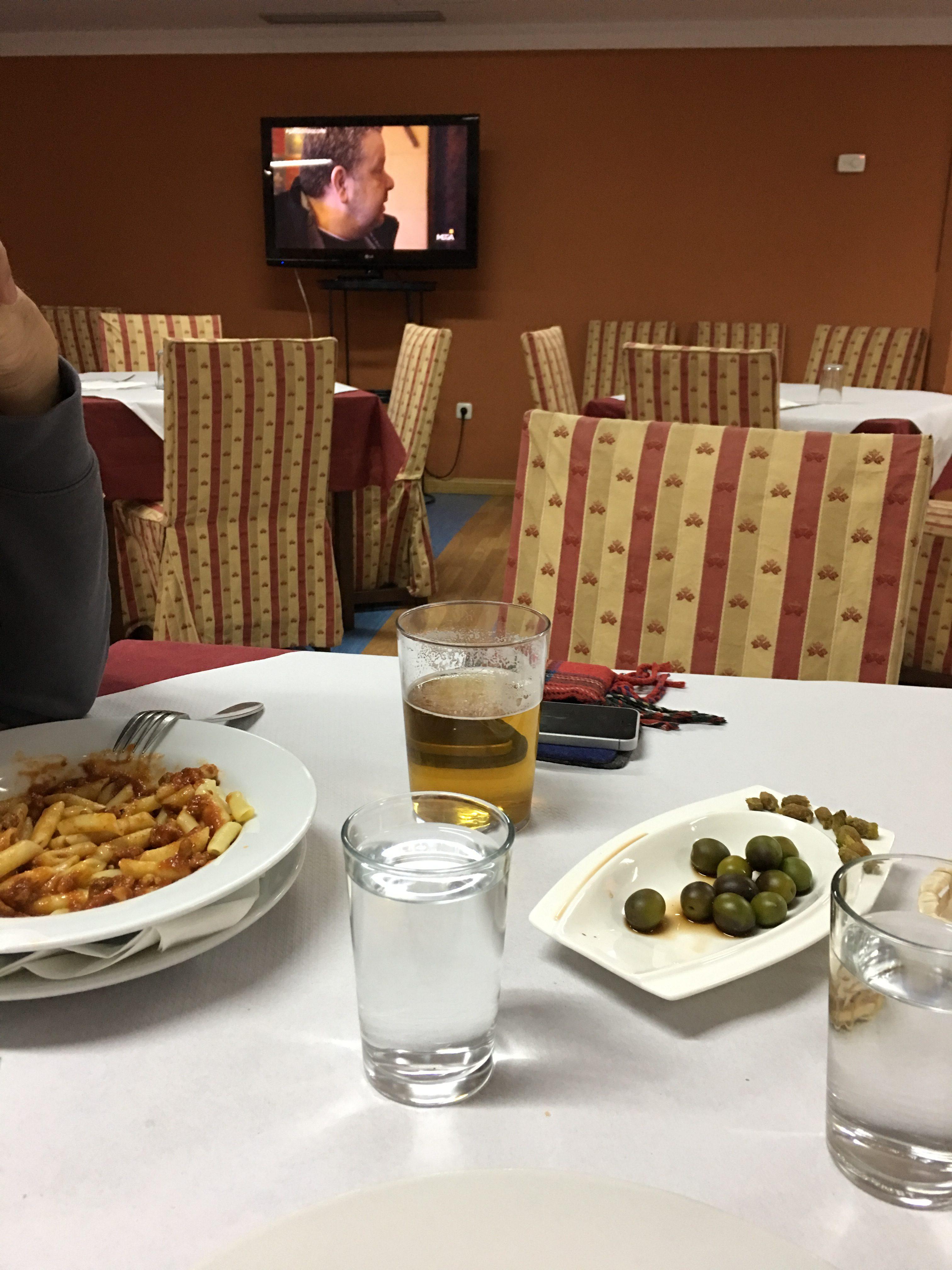 Restaurant mit Essen auf dem Tisch. Im Hintergrund läuft ein Fernseher