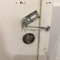 Improvisierter Riegel an einer Toilettentür. Man sieht anhand der Schraubenlöcher, dass es schon andere Verriegelungen gab.