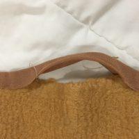 Die Naht der Einfassung einer Wolldecke ist aufgegangen