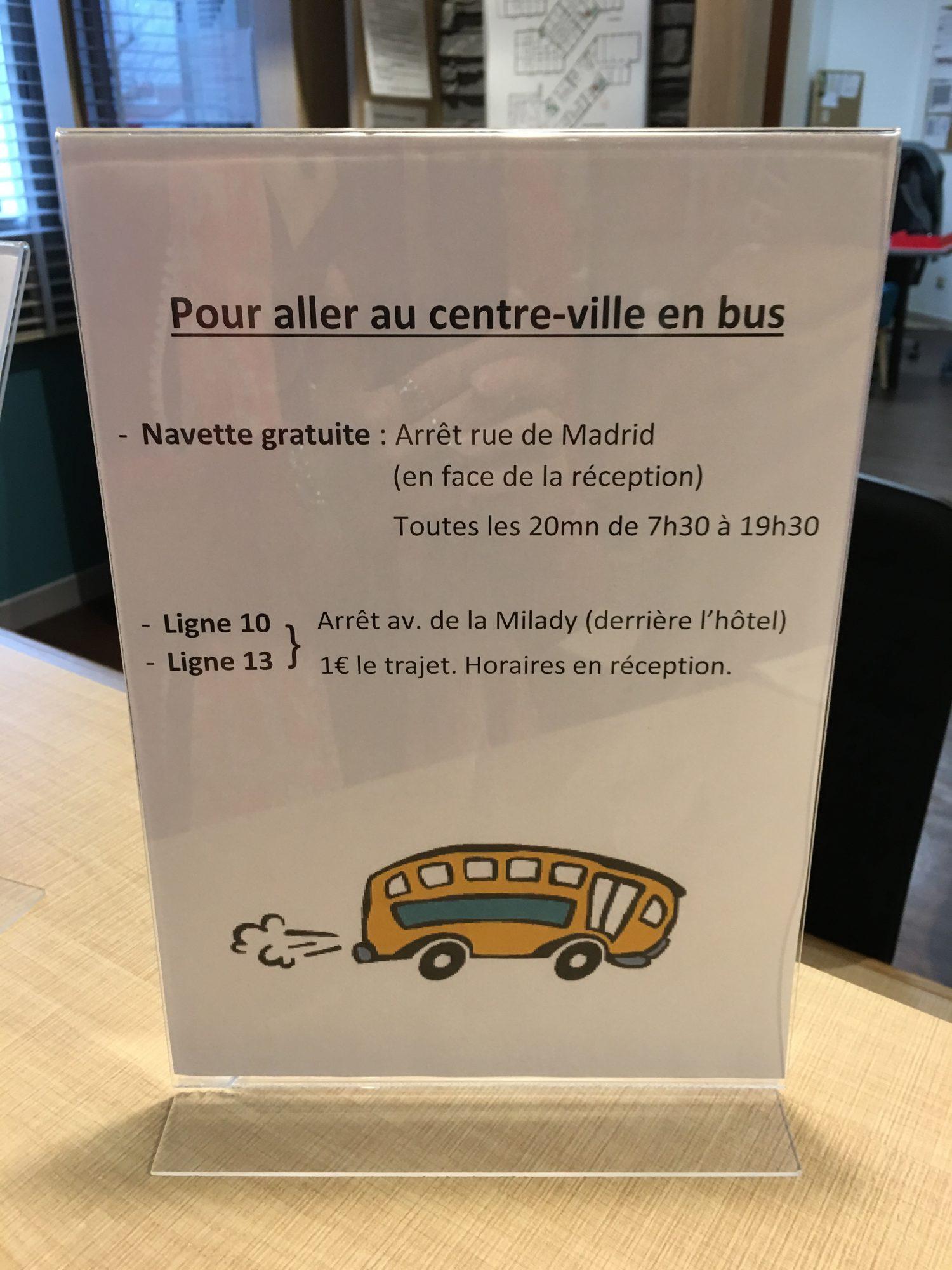 Aufsteller an einer Rezeption beschreibt Busverbindungen in die Stadt in französischer Sprache