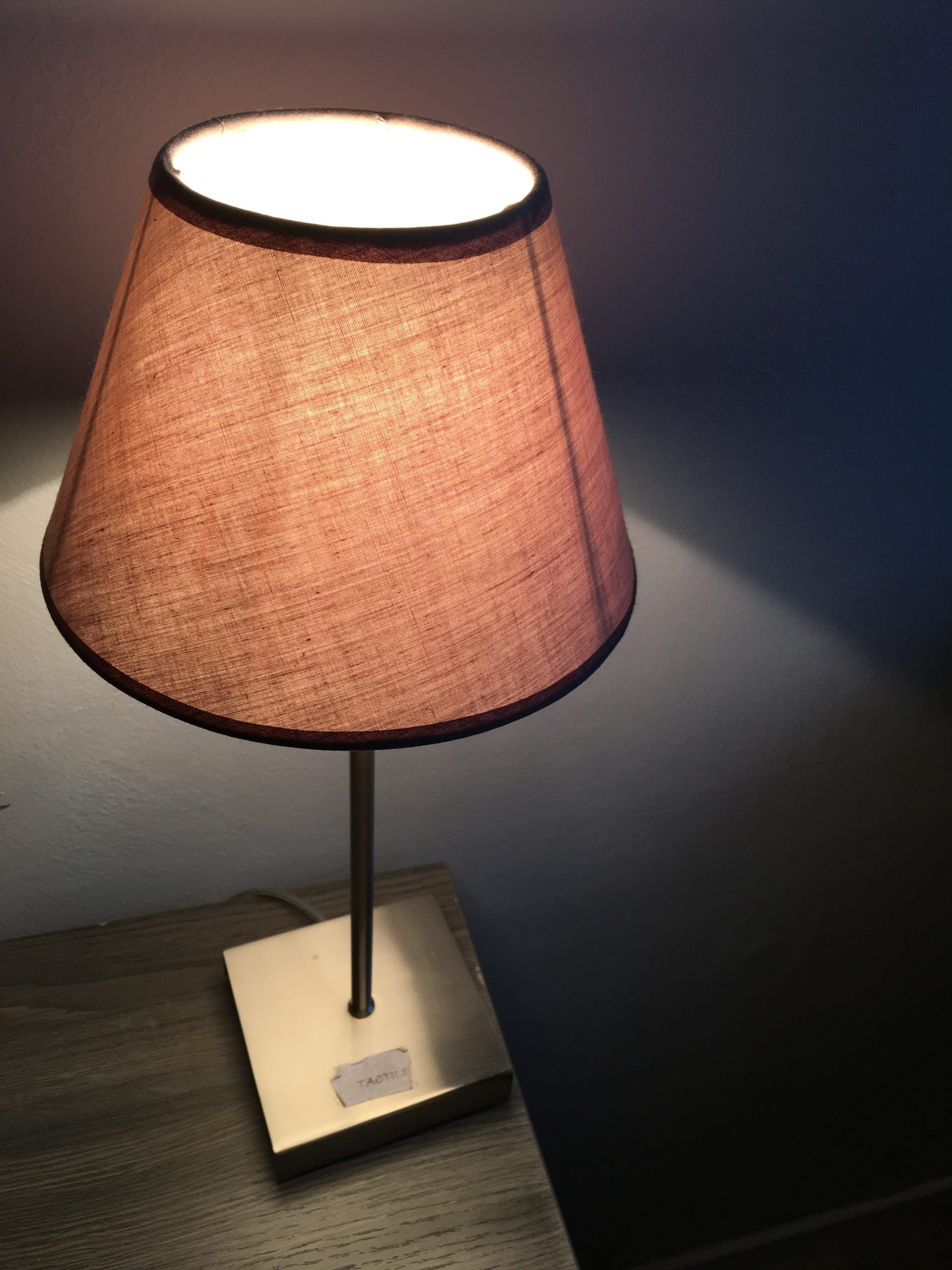 Nachttischlampe mit Fuß auf dem ein Aufkleber klebt: tactile