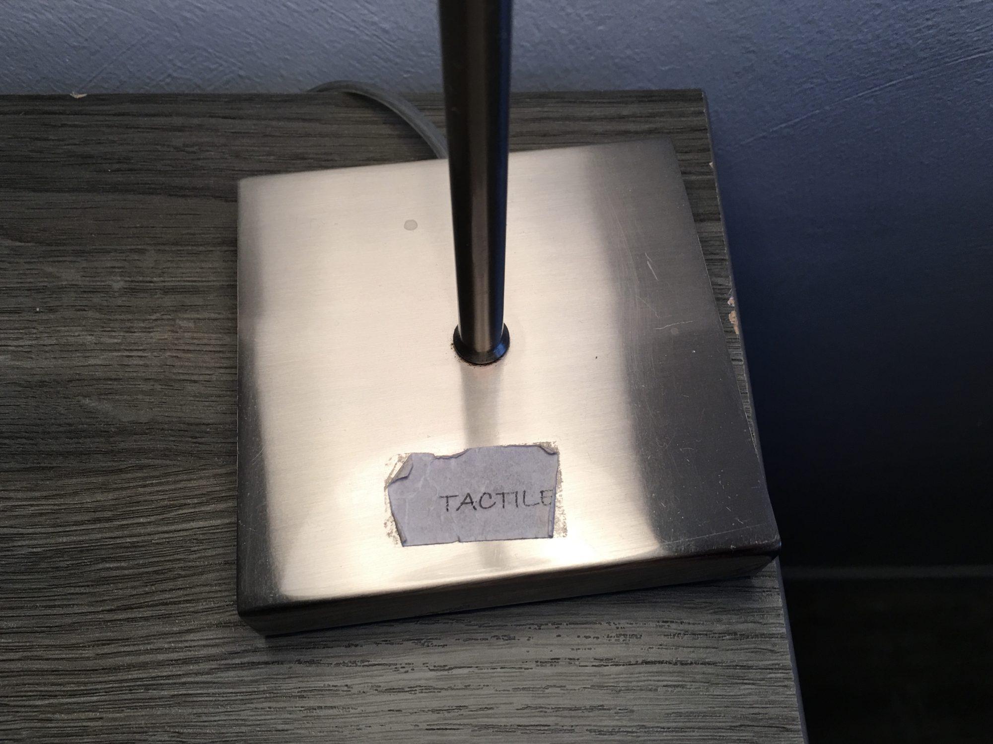 Aufkleber auf dem Fuß einer Nachttischlampe: tactile