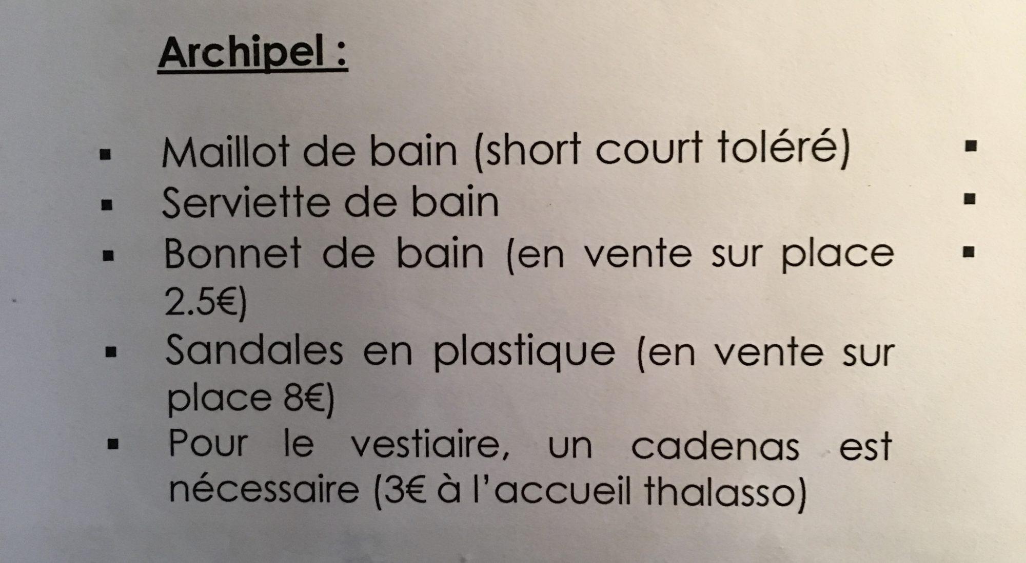 Französischer Text beschreibt, was man im Spa braucht. Badehaube, Plastikschuhe, Handtuch und Vorhängeschloss
