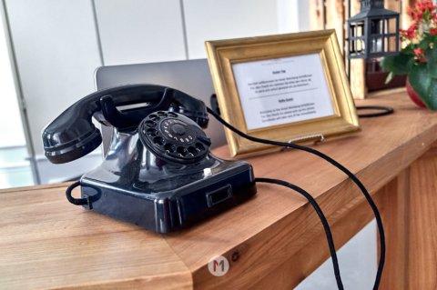 Altes Telefon mit Wählscheibe an der Rezeption